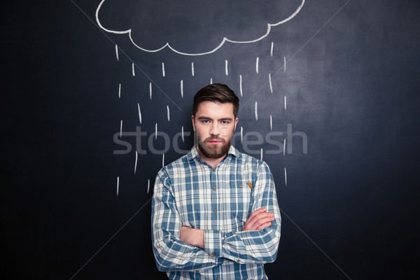 Serious man standing under the drawn rain over chalkboard background  Stock photo © deandrobot