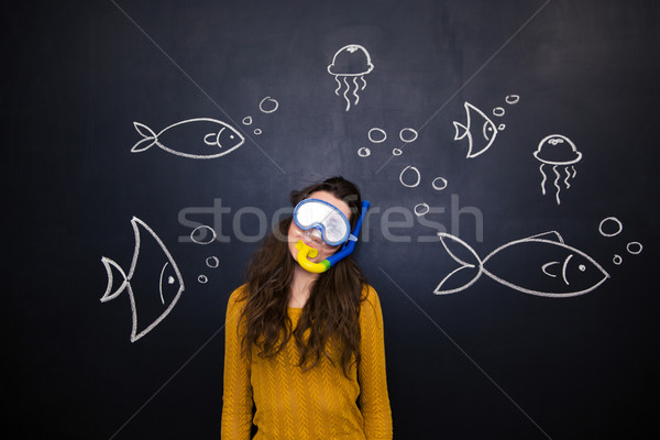Pretty woman in diving mask over chalkboard with underwater world Stock photo © deandrobot