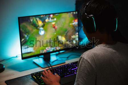 Concentrated gamer in headphones using computer for playing game  Stock photo © deandrobot