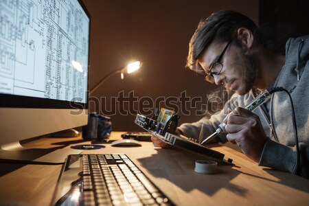 Concentrated man looking at scheme on monitor and repairing motheboard  Stock photo © deandrobot