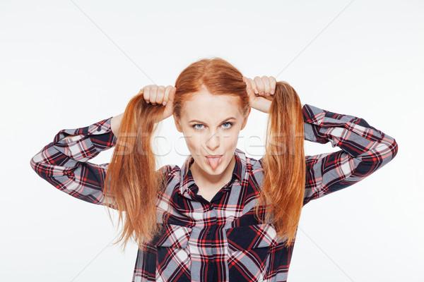 Vörös hajú nő nő mutat nyelv tart izolált Stock fotó © deandrobot