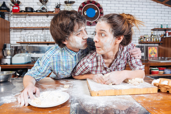 Amusing couple making funny faces on kitchen together Stock photo © deandrobot