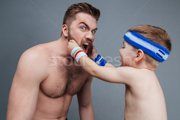 Smiling little son playing with dad beard Stock photo © deandrobot