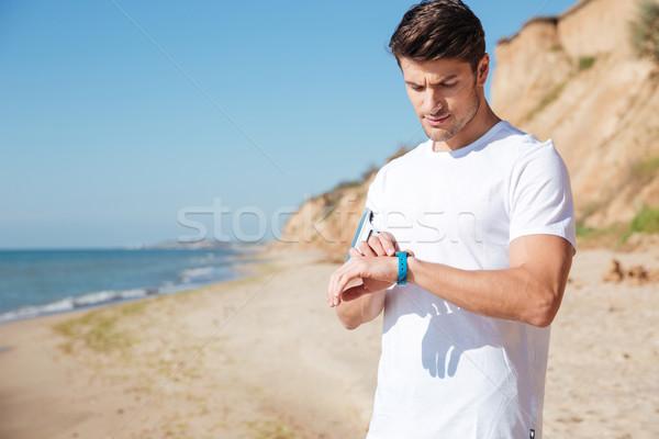 Sportsman using activity tracker on the beach Stock photo © deandrobot