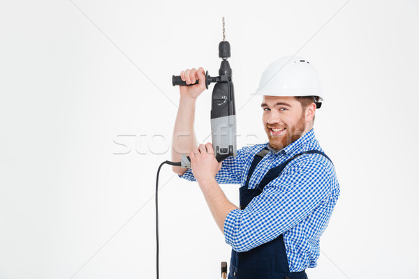 Cheerful young worker in helmet using drill and pointing up Stock photo © deandrobot