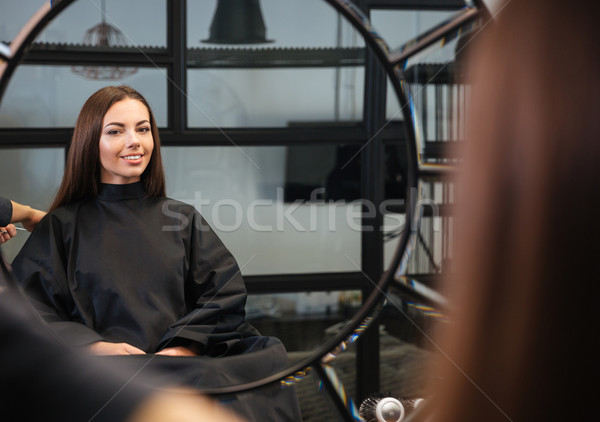 Mirror reflection of young woman getting her hairdo by stylist Stock photo © deandrobot