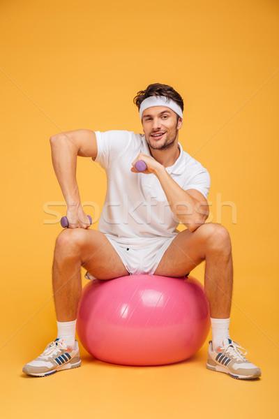 Smiling sportsman sitting on the fitness ball holding dumbbells Stock photo © deandrobot