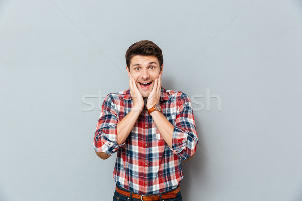 Surprised excited man in plaid shirt standing with mouth opened Stock photo © deandrobot