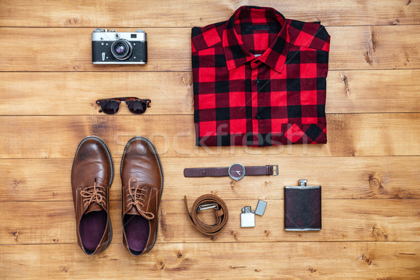 Travel concept shirt, camera, shoes, flask, watch, shoes on desk Stock photo © deandrobot