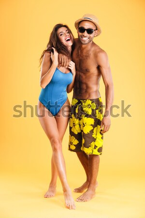 Smiling multiracial couple holding bottles and showing thumbs up gesture Stock photo © deandrobot