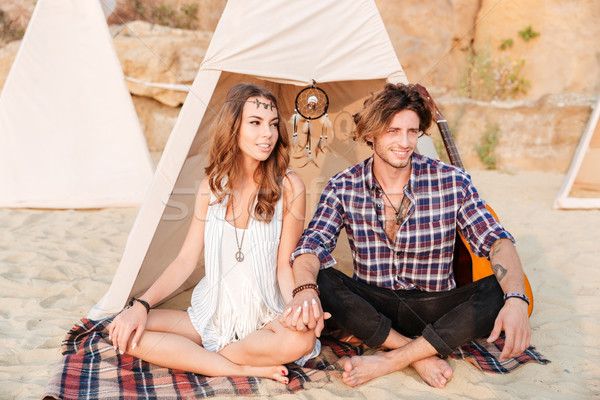 Coppia seduta gambe incrociate spiaggia tenda giovani Foto d'archivio © deandrobot