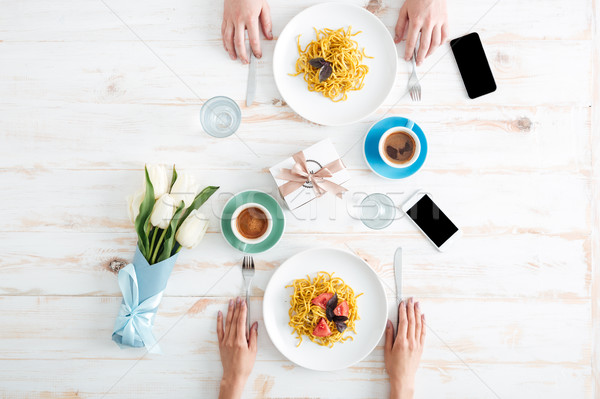 Hands of couple eating pasta and drinking coffee on table Stock photo © deandrobot