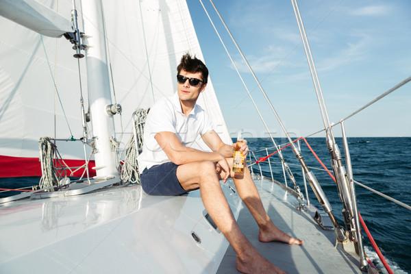 Jóképű fiatalember iszik sör pihen jacht Stock fotó © deandrobot