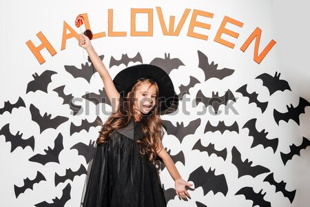 Beautiful blonde young woman in witch costume standing and laughing Stock photo © deandrobot