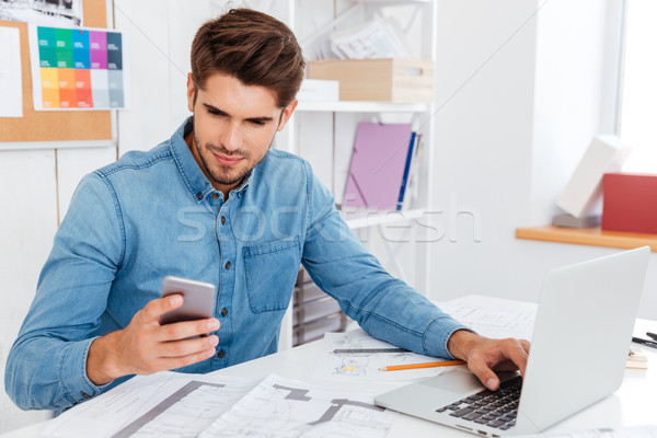 Smiling young businessman in glasses usingat workplce Stock photo © deandrobot