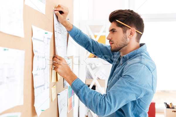 Serius casual businessman posting business plan at the office board Stock photo © deandrobot