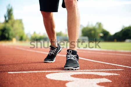Legs of young sportsman running on stadium track Stock photo © deandrobot