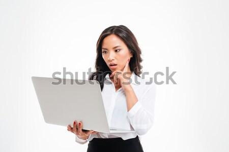 Uimit inteligent asiatic femeie de afaceri uita laptop Imagine de stoc © deandrobot