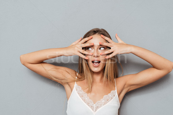Young scared woman looking away through fingers Stock photo © deandrobot