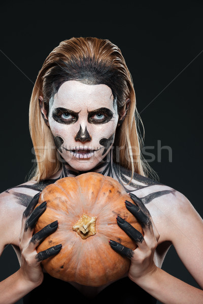 Closeup of woman with gothic skeleton makeup holding pumpkin Stock photo © deandrobot