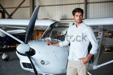 Cheerful young man standing with arms crossed near the airplane Stock photo © deandrobot