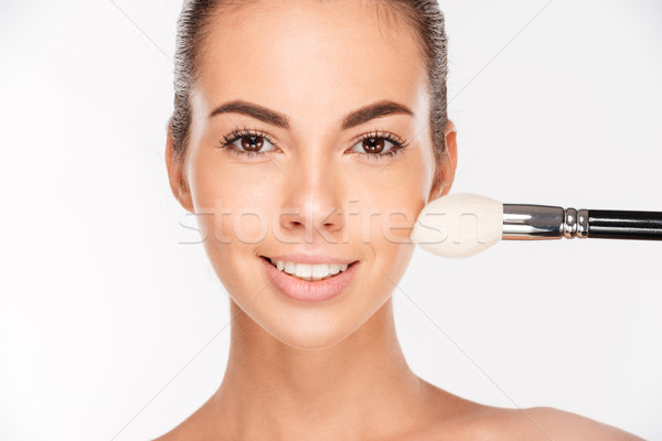 Beautiful young woman apply powder on her face Stock photo © deandrobot