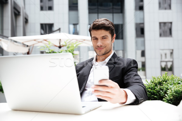 Smiling young businessman with laptop sitting and using mobile phone Stock photo © deandrobot