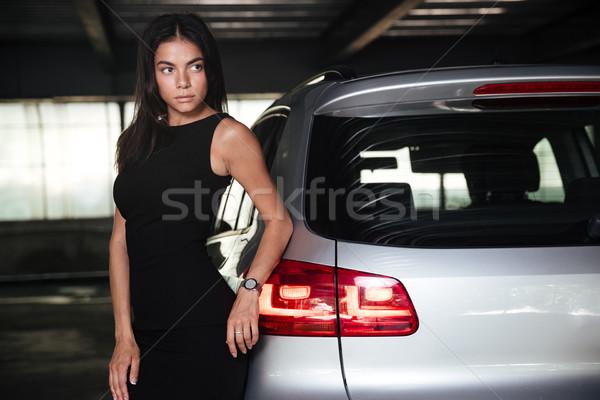 Business woman standing near her car on parking Stock photo © deandrobot