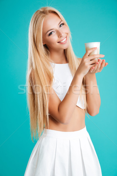 Smiling blonde woman with long hair drinking coffee to go Stock photo © deandrobot