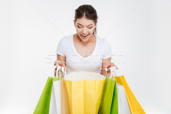 Woman holding purchasings after shopping and looking on them Stock photo © deandrobot