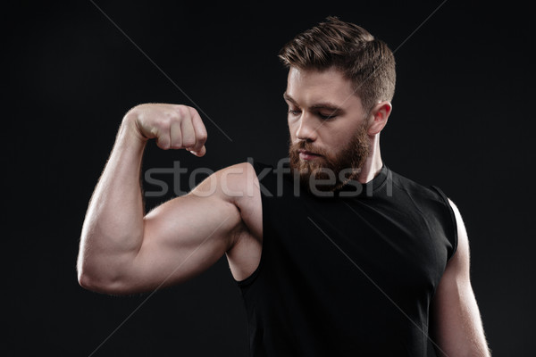 Fitness man demonstrates bicep Stock photo © deandrobot