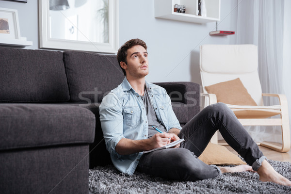 Young casual man thinking about something and making notes Stock photo © deandrobot