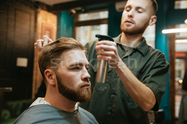 Hipster man getting haircut by hairdresser while sitting in chair. Stock photo © deandrobot
