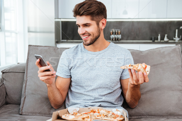 Happy young man chatting and eating pizza Stock photo © deandrobot