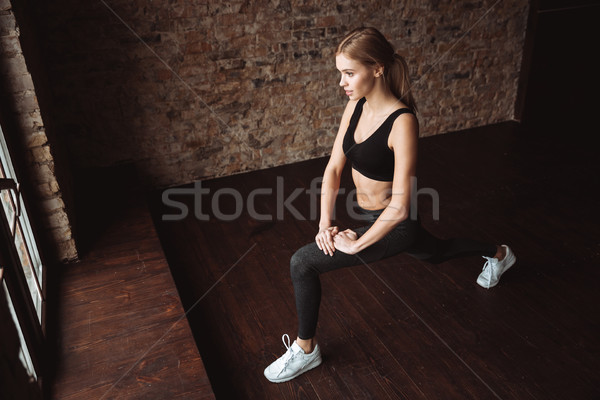 Attractive fitness lady make sport exercises in gym Stock photo © deandrobot