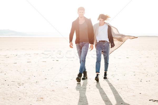 Full length portrait of smiling happy couple walking along seashore Stock photo © deandrobot