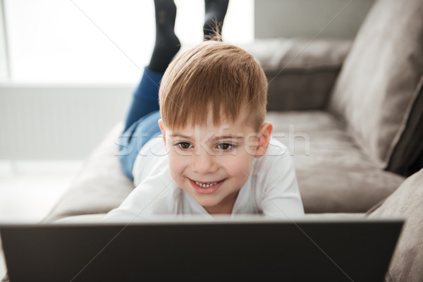 Smiling boy using laptop while lies on sofa at home Stock photo © deandrobot