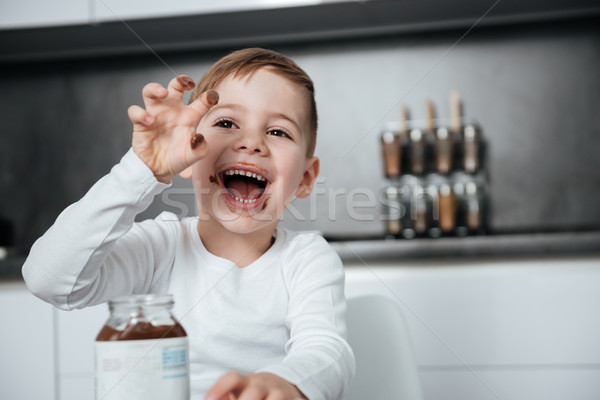 Happy boy standing in the kitchen while eating sweeties Stock photo © deandrobot