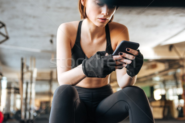 Woman athlete sitting and using smartphone in gym Stock photo © deandrobot