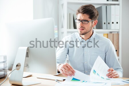 Concentrated young bearded businessman using computer Stock photo © deandrobot