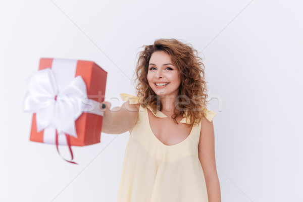 Happy woman in singlet showing gift at camera Stock photo © deandrobot