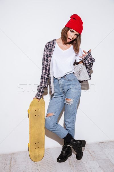 Lady make rock gesture and holding skateboard Stock photo © deandrobot