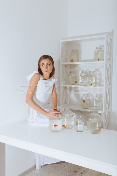 Woman sitting on table and holding jar with gold fish Stock photo © deandrobot