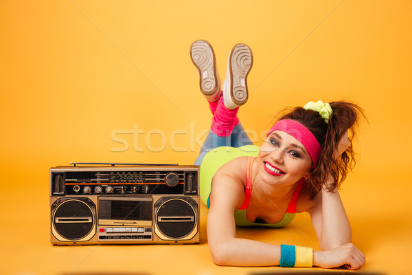 Smiling beautiful young fitness woman lying near retro boombox Stock photo © deandrobot