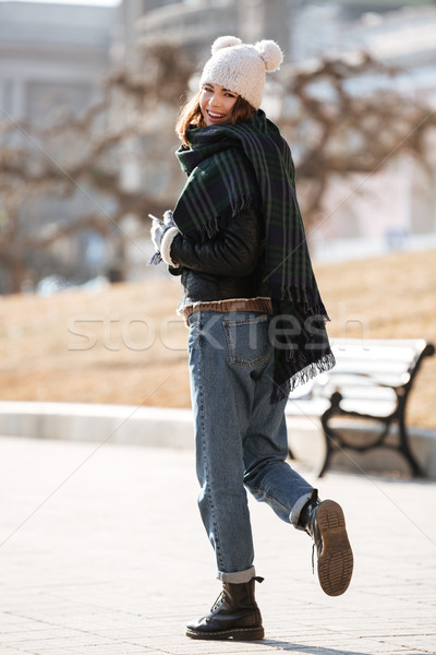 Cheerful woman walking and looking back in the city in autumn Stock photo © deandrobot