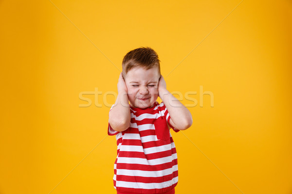 Portrait of an angry unhappy irritated little boy covering ears Stock photo © deandrobot
