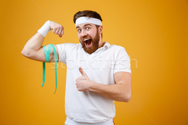 Portrait of a happy excited fitness man measuring his biceps Stock photo © deandrobot