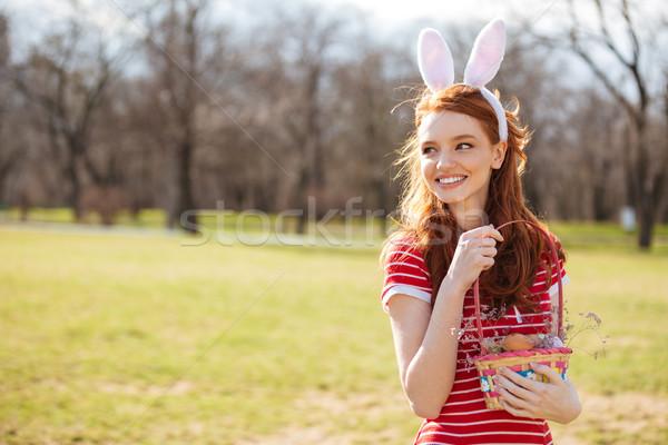 Portrait of red head woman wearing bunny ears Stock photo © deandrobot