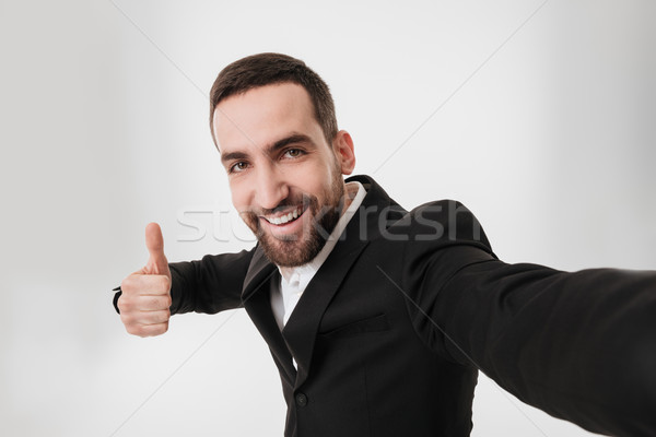 Happy businessman make a selfie and showing thumbs up gesture. Stock photo © deandrobot