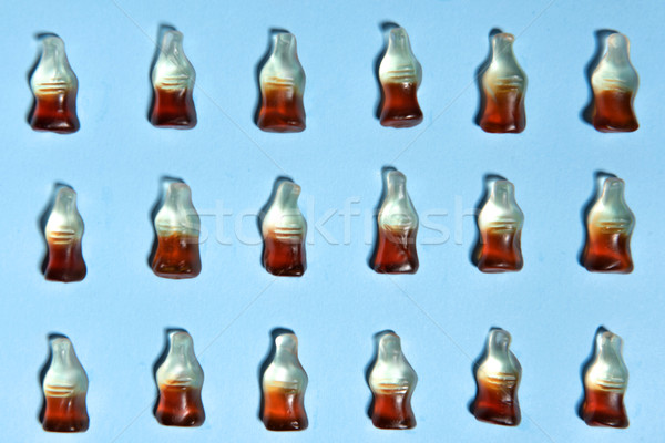 Candy in bottle form over blue table background. Stock photo © deandrobot